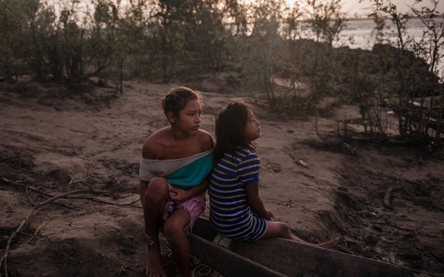 Girls waiting for fishermen to arrive with a catch that they can take home, in Parmana, a fishing village on the banks of the Orinoco River in central Venezuela, on Dec 4, 2019. The New York Times