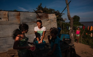 A family prepares lunch in Parmana, a fishing village on the banks of the Orinoco River in central Venezuela, on Dec 3, 2019. The New York Times