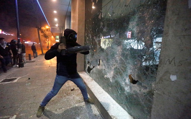Protesters smash the window of a bank as demonstrations against the government continue in Beirut, Lebanon January 14, 2020. REUTERS