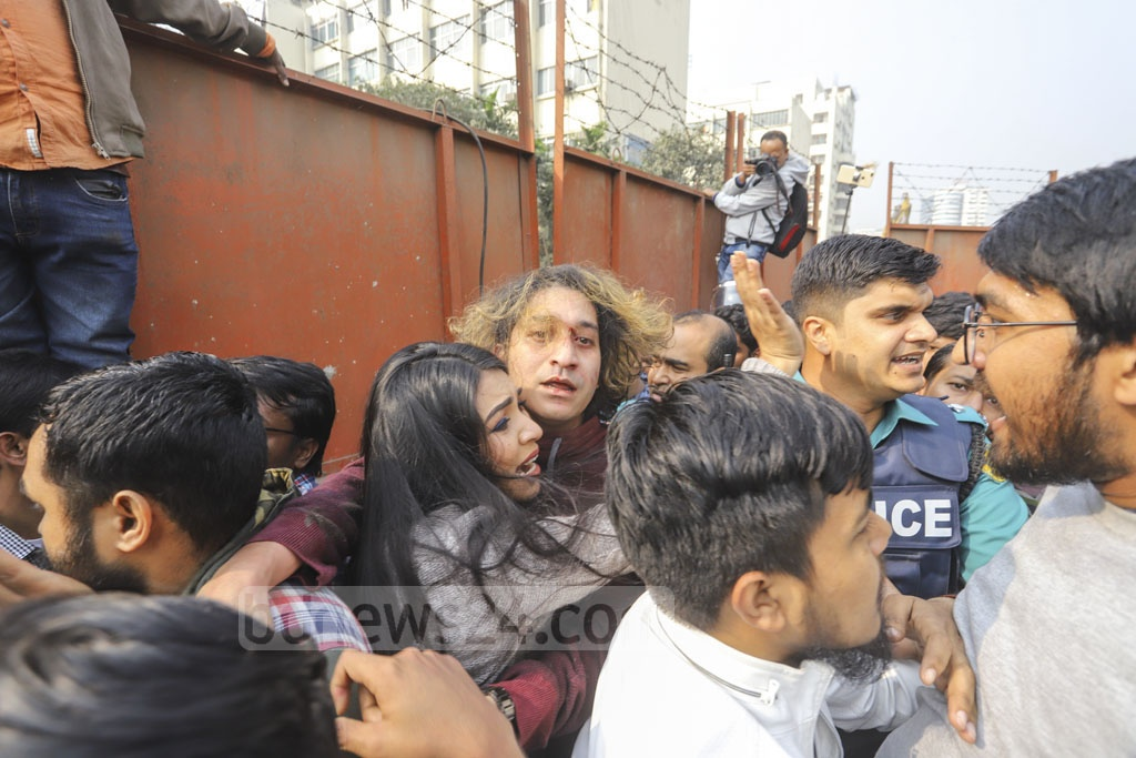 A woman trying to save her husband from angry protesters who were beating him after he pulled a gun on the demonstrators at Shahbagh in Dhaka on Wednesday. Photo: Asif Mahmud Ove