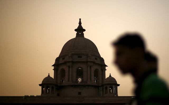 A commuter walks past the building of India's Ministry of Finance during dusk in New Delhi, India, May 18, 2015. REUTERS
