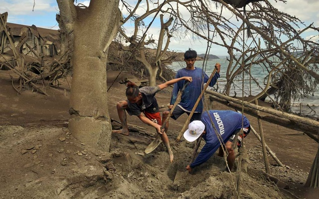 Residents dig for belongings as the village of Calauit is buried in ash on Taal Volcano island in the Philippines on Tuesday, Jan 14, 2020. The New York Times