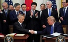 Chinese Vice Premier Liu He and US President Donald Trump shake hands after signing