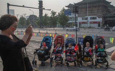 Babies hold Chinese flags in their strollers in Beijing, Oct 1, 2019, as China celebrates 70 years of Communist Party rule. The number of babies born in China last year fell to a nearly six-decade low, exacerbating a looming demographic crisis that is set to reshape the world's most populous nation and threaten its economic vitality. The New York Times