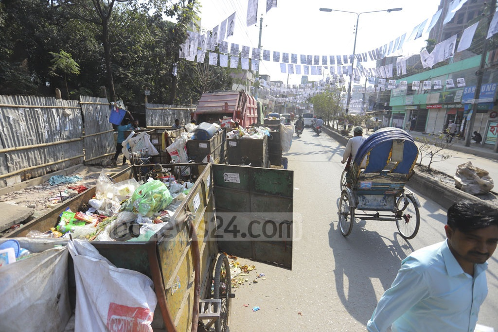Dhaka City Corporation workers collect waste on the 60 feet road in Mirpur's Pirerbagh area much to the dismay of pedestrians who have to deal with the stench. Photo: Asif Mahmud Ove