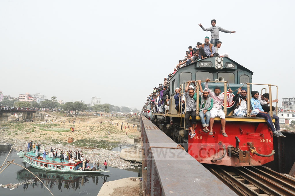 People risking their lives to return home on the roof of a train at the end of the second phase of the Bishwa Ijtema on Sunday.