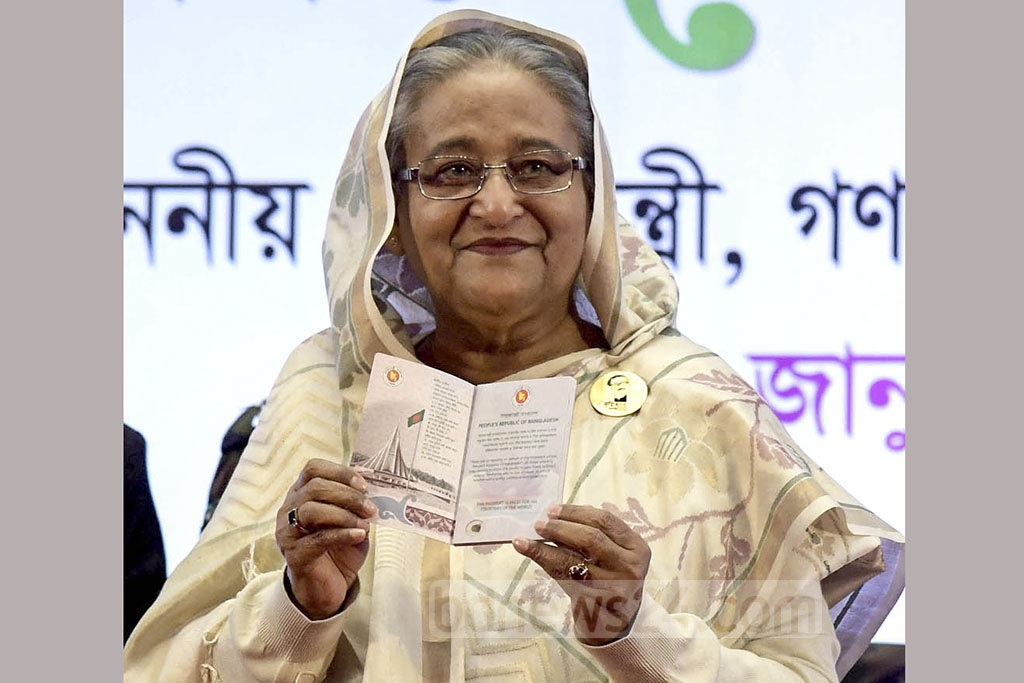 Prime Minister Sheikh Hasina shows her electronic passport after inaugurating the distribution at the Bangabandhu International Conference Centre in Dhaka on Wednesday. Photo: PID