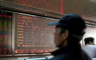 An investor looks at a stock quotation board at a brokerage office in Beijing, China January 3, 2020. REUTERS