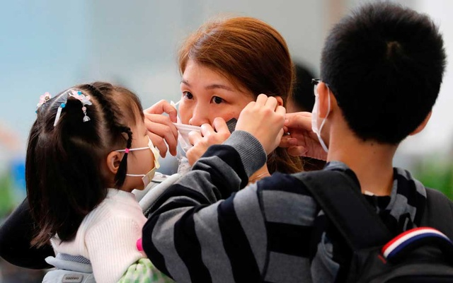 A woman adjusts her mask to prevent an outbreak of a new coronavirus at the Hong Kong West Kowloon High Speed Train Station, in Hong Kong, China Jan 23, 2020. REUTERS