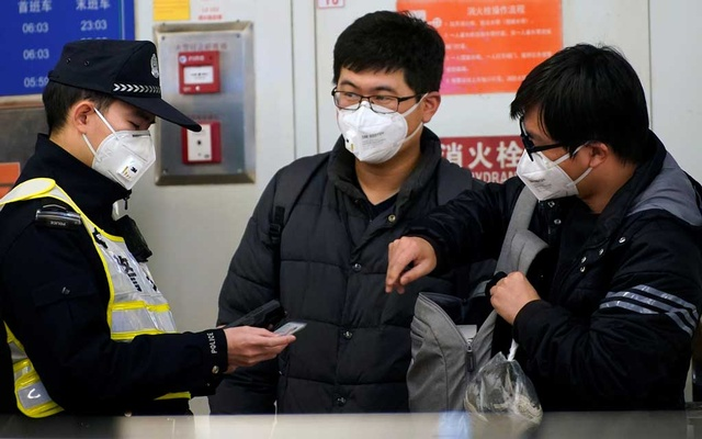 A police officer wearing a protective mask checks identity cards at a subway station in Shanghai, China Jan 23, 2020. REUTERS