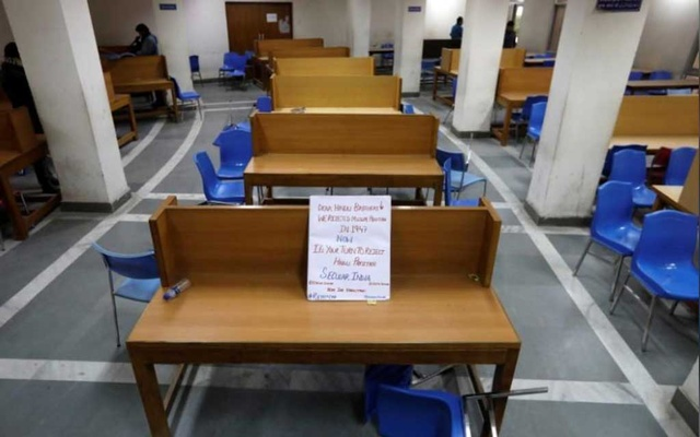 FILE PHOTO: A placard lies on a table inside a partially damaged library of the Jamia Millia Islamia university after police entered the university campus on the previous day, following a protest against a new citizenship law, in New Delhi, India, Dec 16, 2019. REUTERS/Adnan Abidi