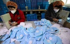 Workers make protective masks at a factory in Handan, Hebei province, China January 22, 2020. Picture taken January 22, 2020. China Daily via REUTERS