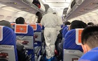 Health workers in protective suits check the condition of a passenger on an airplane that just landed from Changsha, a city in a province neighbouring the centre of coronavirus outbreak Hubei province, in Shanghai, China January 25, 2020. Reuters