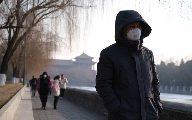 People wearing protective masks walk outside Forbidden City which is closed to visitors, according to a notice in its main entrance for the safety concern following the outbreak of a new coronavirus, in Beijing, China January 25, 2020. Reuters