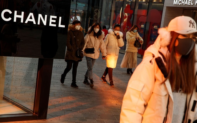 People wearing face masks walk past luxury boutiques in the Sanlitun shopping district in Beijing, China, as the country is hit by an outbreak of the new coronavirus, Jan 25, 2020. REUTERS