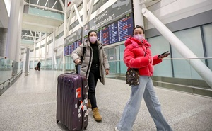 Travellers wear masks at Pearson airport arrivals, shortly after Toronto Public Health received notification of Canada's first presumptive confirmed case of coronavirus, in Toronto, Ontario, Canada Jan 25, 2020. REUTERS/Carlos Osorio