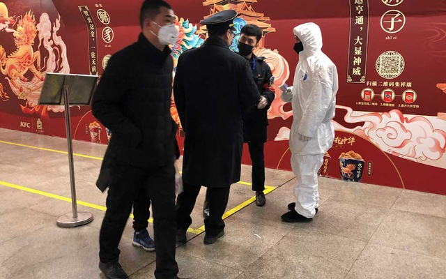 A worker in a protective suit speaks with staff members at the Wangfujing subway station, as the country is hit by an outbreak of the new coronavirus, in Beijing, China January 26, 2020. Reuters