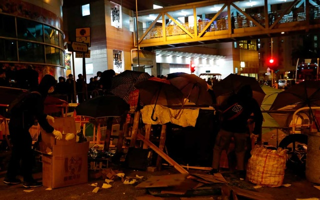 Anti-government protesters set up a barrier to block the road outside of a newly built residential building in Hong Kong that authorities planned to use as a quarantine facility, as public fears about the coronavirus outbreak intensify, in Hong Kong, China January 26, 2020. Reuters
