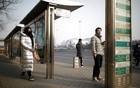 People wearing face masks stand at a bus stop, as the country is hit by an outbreak of the new coronavirus, in Beijing, China Jan 27, 2020. REUTERS