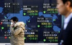 People walk past an electronic display showing world markets indices outside a brokerage in Tokyo, Japan, January 8, 2020. REUTERS