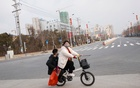 People wear face masks as they cycle in an empty street in the Yunxi county, Hunan province, near the border to Hubei province, on virtual lockdown after an outbreak of a new coronavirus, in China, Jan 28, 2020. REUTERS