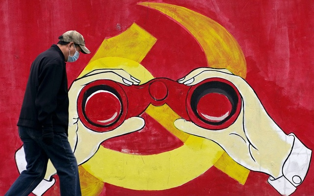 A man wears a mask as he walks past a mural showing a modified image of the Chinese Communist Party emblem in Shanghai, China Jan 28, 2020. REUTERS