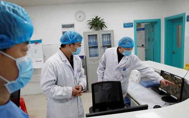 Doctors look at a screen that shows the ward where patients who are infected with the coronavirus are treated at the First People's Hospital in Yueyang, Hunan Province, near the border to Hubei Province, which is under partial lockdown after an outbreak of a new coronavirus, in China January 28, 2020. Reuters