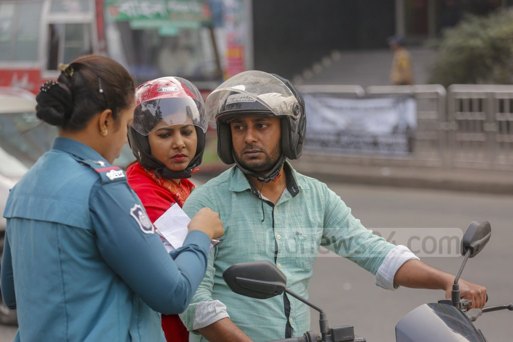 A traffic policewoman fining a motorcycle rider in Dhanmondi 27 amid a ban on the two-wheelers on Friday due to Dhaka city polls. Photo: Mahmud Zaman Ovi