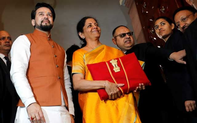 India's Finance Minister Nirmala Sitharaman is flanked by junior Finance Minister Anurag Thakur as she arrives to present the budget in Parliament in New Delhi, India, Feb 1, 2020. REUTERS