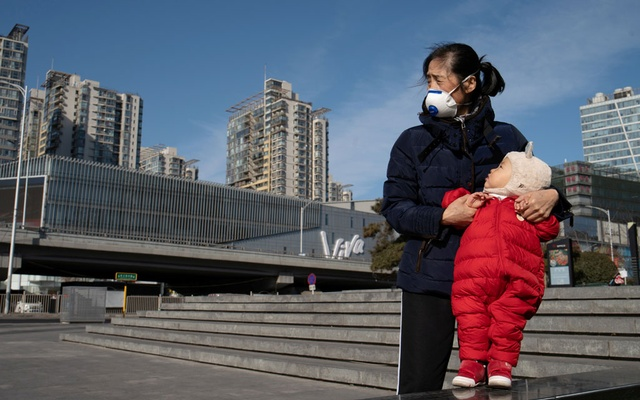 A woman wearing a face mask holds a child near a shopping mall in Beijing, China, as the country is hit by an outbreak of the new coronavirus, February 1, 2020. REUTERS