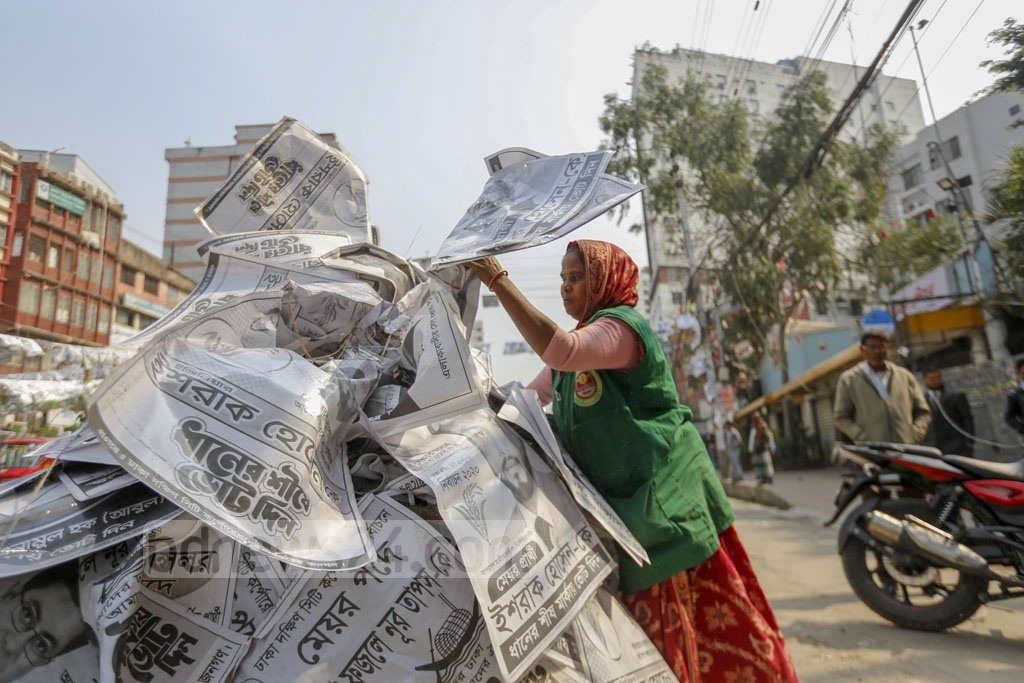Dhaka had turned into a city of posters during the run-up to the Feb 1 polls. City corporation workers launched a drive on Sunday to make the city clean by removing those posters. Photo: Mahmud Zaman Ovi