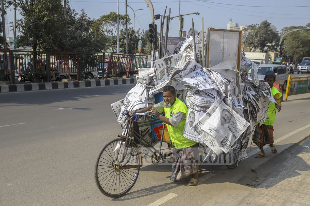 Dhaka had turned into a city of posters during the run-up to the Feb 1 polls. City corporation workers launched a drive on Sunday to make the city clean by removing those posters. Photo: Asif Mahmud Ove
