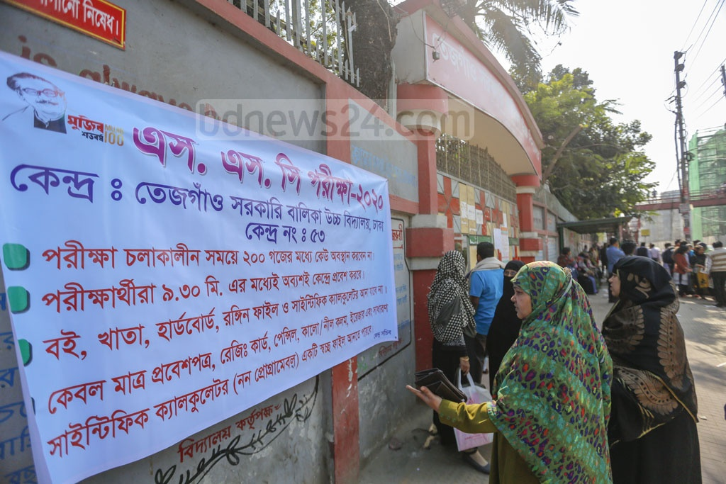 Guardians of SSC examinees reading a notice on the exam rules outside the Tejgaon Government Girl's High School centre in Dhaka. Photo: Mahmud Zaman Ovi