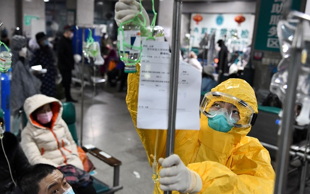 A medical worker in protective suit adjusts a drip bag for a patient at a hospital, following an outbreak of the new coronavirus in Wuhan, Hubei province, China Feb 3, 2020. REUTERS