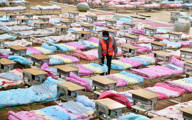 A worker sets up beds at the Hongshan Stadium to convert it into a makeshift hospital following an outbreak of the new coronavirus, in Wuhan, Hubei province, China Feb 4, 2020. REUTERS