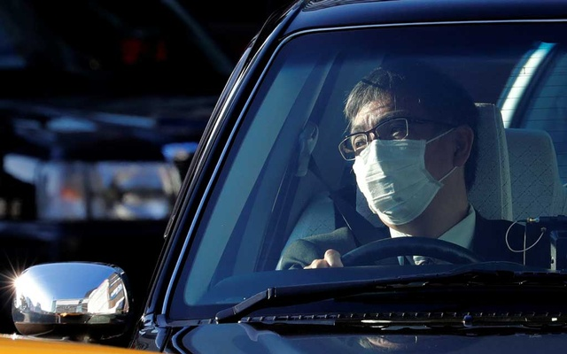 A taxi driver wearing a surgical mask sits inside a taxi in front of Yokohama station in Yokohama, south of Tokyo, Japan Feb 5, 2020. REUTERS