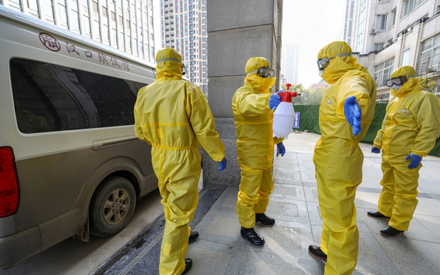Funeral parlour staff members in protective suits help a colleague with disinfection after they transferred a body at a hospital, following the outbreak of a new coronavirus in Wuhan, Hubei province, China Jan 30, 2020. REUTERS