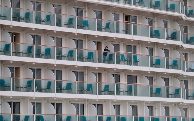 A passenger wearing face mask looks out from a cabin on the World Dream cruise ship, after it had been denied entry in Taiwan amid concerns of coronavirus infection on board, is seen docked at the Kai Tak Cruise Terminal in Hong Kong, China Feb 5, 2020. REUTERS