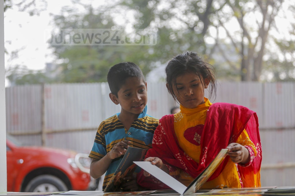 Homeless children see books at the Amar Ekushey Book Fair on Wednesday as it is yet to draw crowds of customers four days after inauguration.