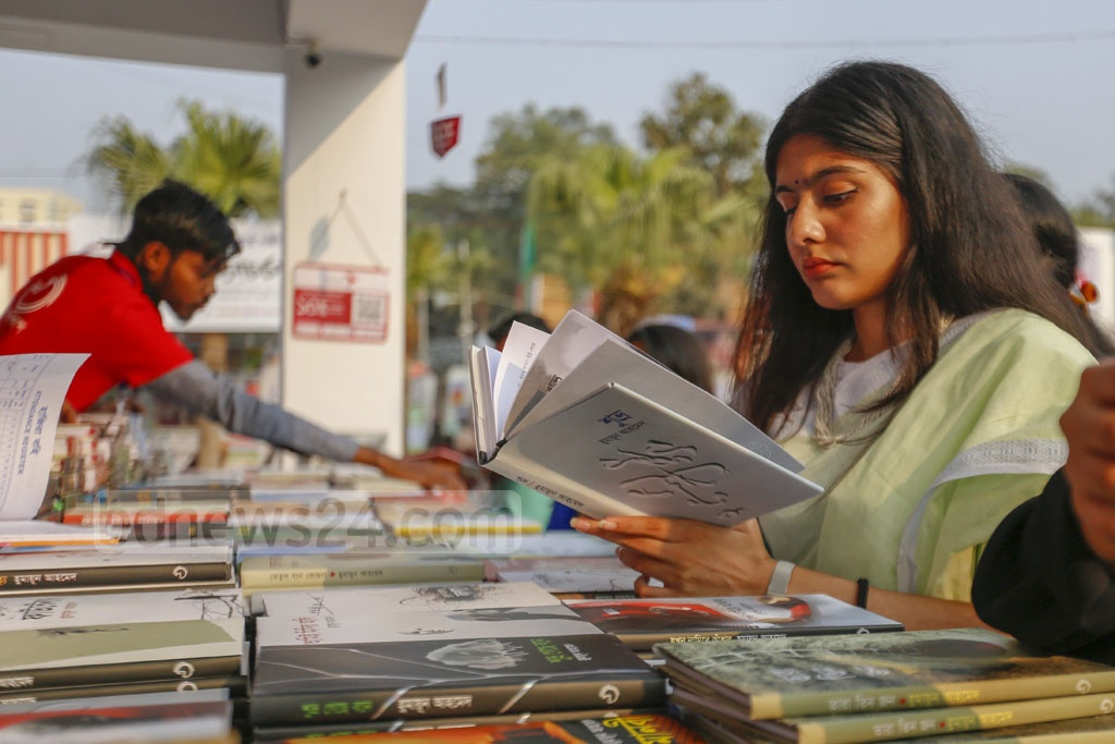 A young woman browsing a book at the Amar Ekushey Book Fair on Wednesday.