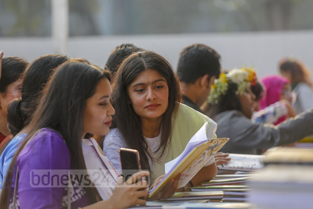 Young women browsing books at the Amar Ekushey Book Fair on Wednesday.