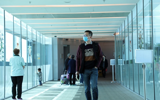 A passenger wearing a mask walks past upon arrival of a flight from Hangzhou, China at Changi Airport, Singapore January 22, 2020. Reuters