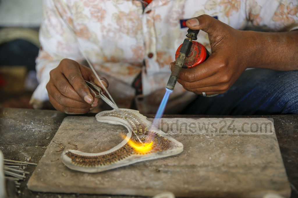 Gas torches have replaced kerosene lamps for the making of jewellery. Many more modern equipment are used now but most of the work is still done by hand. Photo: Mahmud Zaman Ovi