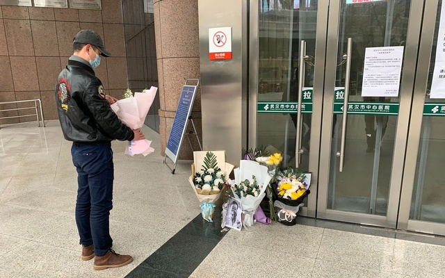 A person stands next to a makeshift memorial for Dr. Li Wenliang at Wuhan City Central Hospital in China, on Feb. 7, 2020. The Chinese public have staged what amounts to an online revolt after the death of Wenliang, who tried to warn of a mysterious virus that has since killed hundreds of people in China, infected tens of thousands and forced the government to corral many of the country's 1.4 billion people. (Chris Buckley/The New York Times)