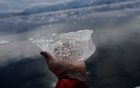 A small block of ice is displayed for a photo, close to Fournier Bay, Antarctica, Feb 3, 2020. REUTERS