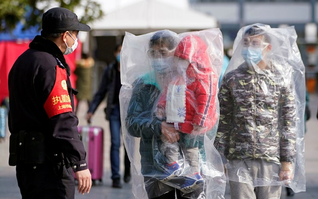 Passengers wearing masks and covered with plastic bags walk outside the Shanghai railway station in Shanghai, China, as the country is hit by an outbreak of a new coronavirus, February 9, 2020. Reuters