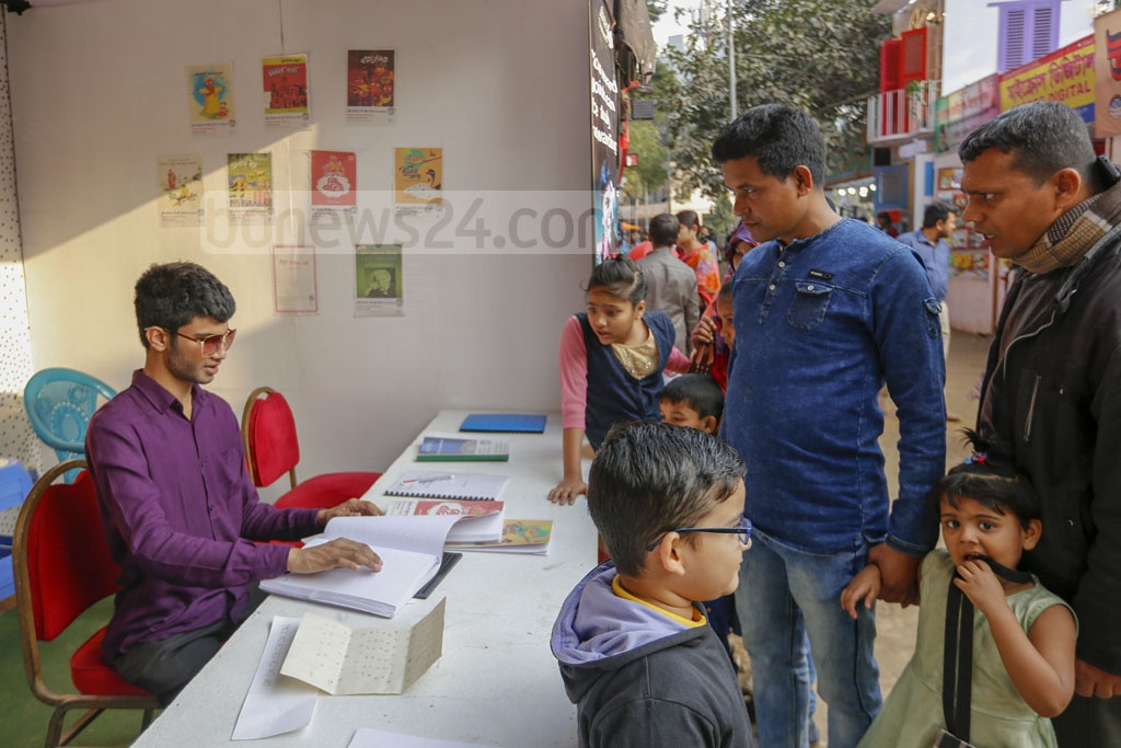 A man with visual impairment reading a braille book at Sporsho Braille Prokashona's stall at the Amar Ekushey Book Fair on Sunday.