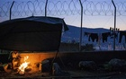 An asylum seeker from Syria tries to stay warm as he prepares dinner for his family in the tent city in Samos, Greece on Jan 12, 2020. The New York Times