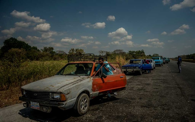 A man pushes his car as he waits in a long line to get gasoline from a government-run gas station in Ospino, Venezuela on Feb 11, 2019. The New York Times