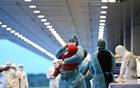 Vietnamese authorities wearing protective suits receive Vietnamese repatriated from Chinese city of Wuhan, at Van Don airport, Quang Ninh province, Vietnam Feb 10, 2020. REUTERS